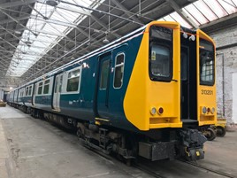Repainted 313201 stands inside Wolverton Works, displaying its newly applied British Rail blue and grey. GTR.